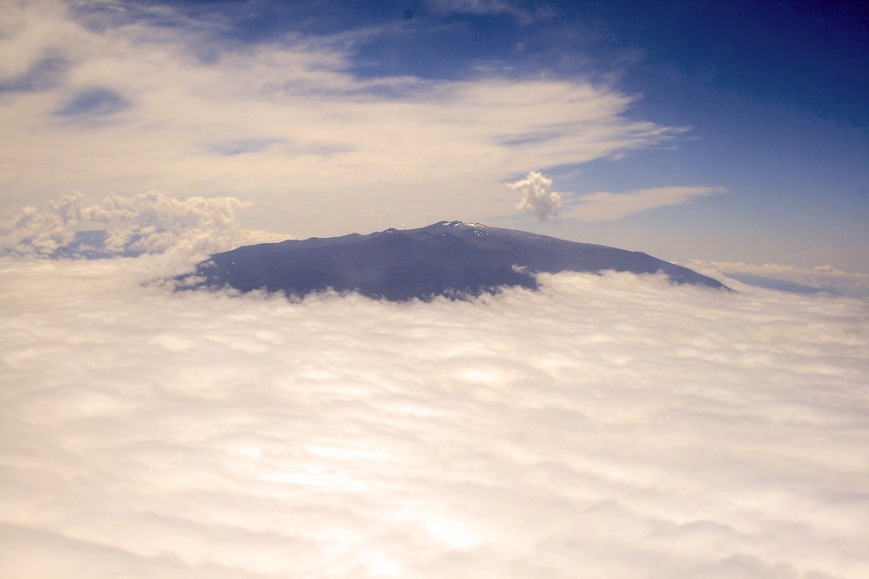 A view of Hawaii's highest peak, Mauna Kea, poking up above the clouds - taken from our airplane.