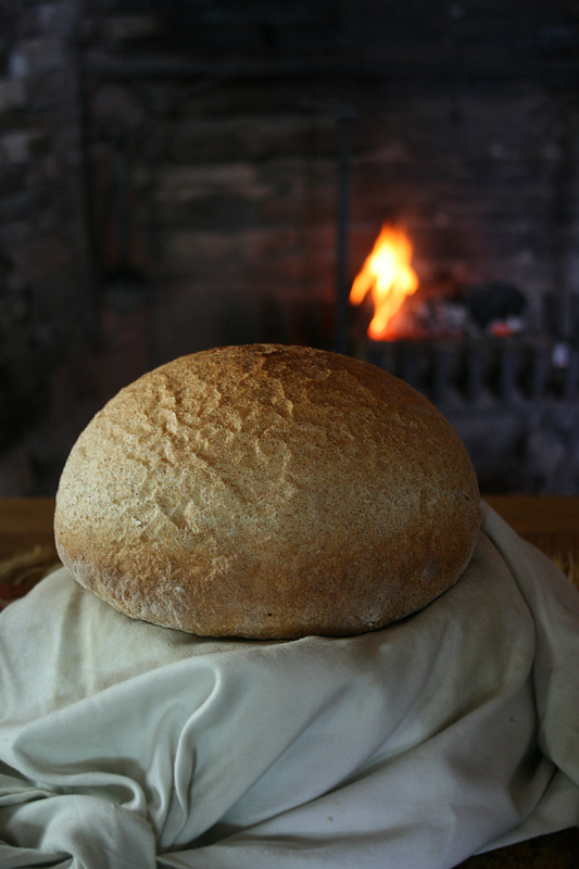 Traditional bread sits on a table at the Colony of Avalon, freshly baked the old-fashioned way in the wood-fired oven behind it.